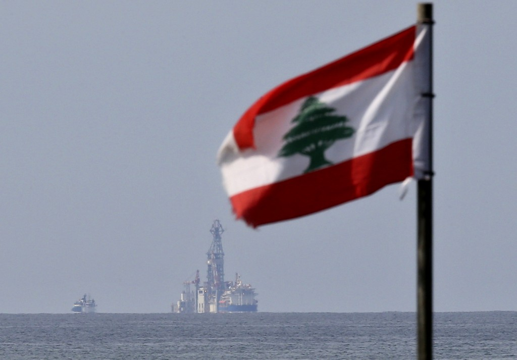 A Lebanese flag flutters in the wind as the drilling ship Tungsten Explorer is seen off the coast of Beirut, Lebanon, Thursday, Feb. 27, 2020. Lebanon...