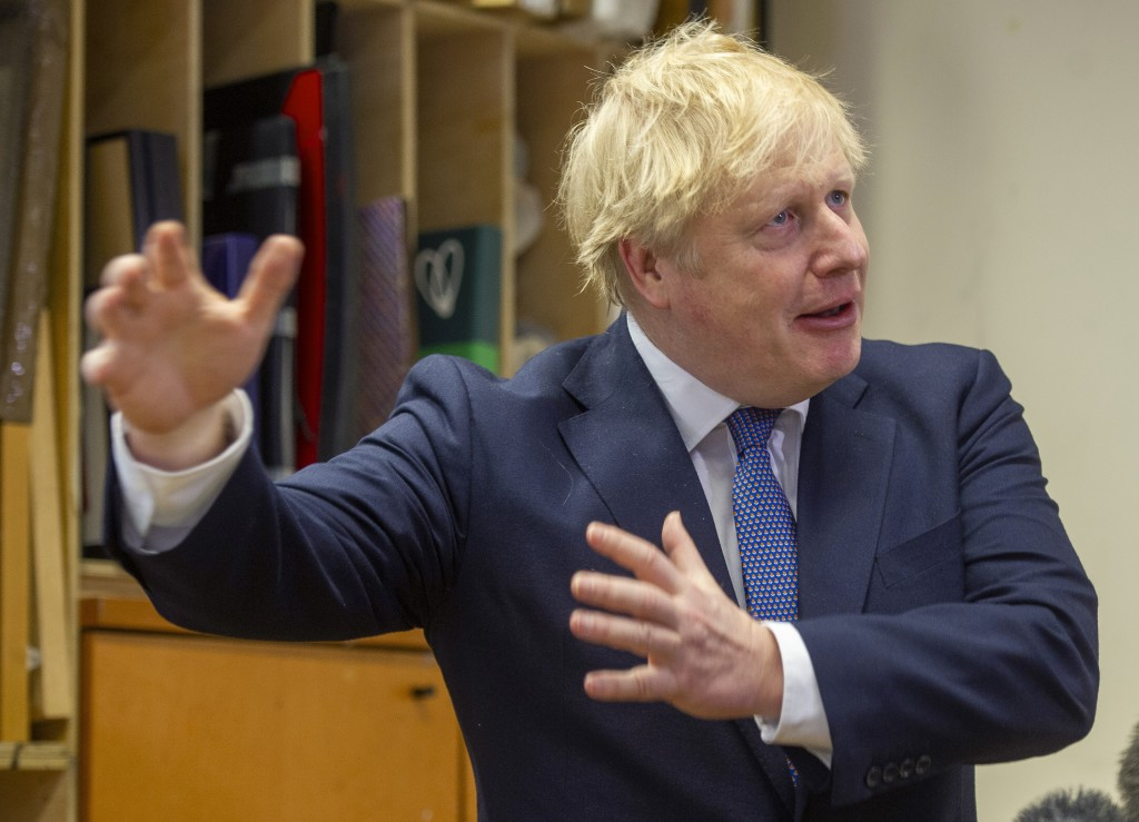 Britain's Prime Minister Boris Johnson gestures during a visit to the Connection, a homelessness centre, at St Martins in the Fields, London, Thursday...