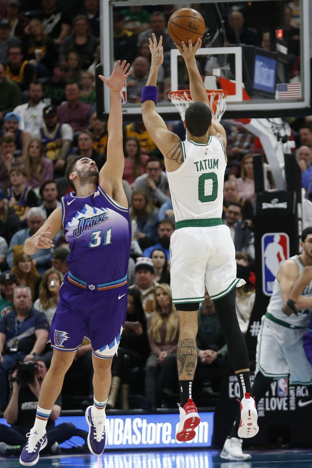 Boston Celtics forward Jayson Tatum (0) shoots as Utah Jazz forward Georges Niang (31) defends during the first half of an NBA basketball game Wednesd...