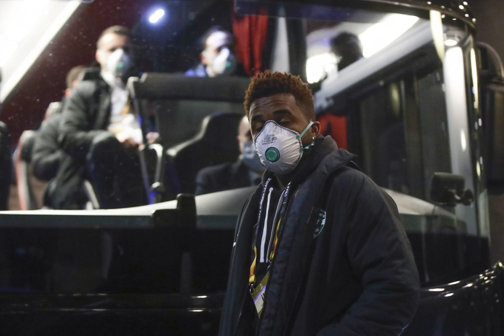 Bulgarian soccer team Ludogorets' Neuciano Gusmao, foregorund, and teammates wearing protective face masks get on a coach bus heading to the San Siro ...