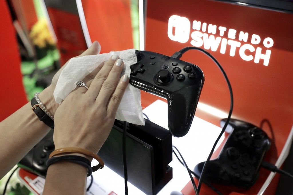 Game demonstrator Alex Chang, of New York, N.Y., hands only, uses a disinfectant wipe to clean a game console at the Nintendo Switch exhibit, Thursday...