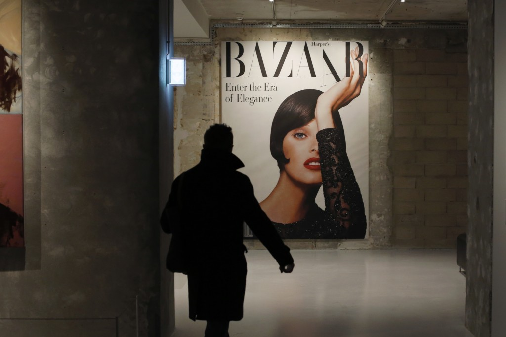 A visit0r walks by a cover from Harper's Bazar magazine as part of the exhibition «Harper's Bazaar, First in Fashion» at the The Musée des Arts Déco...