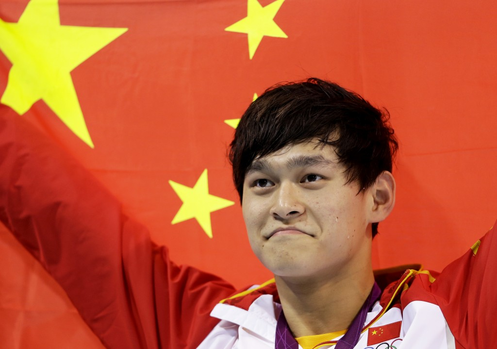 FILE - In this Saturday, Aug. 4, 2012 file photo, China's Sun Yang holds his national flag after winning the gold medal in the men's 1500-meter freest...