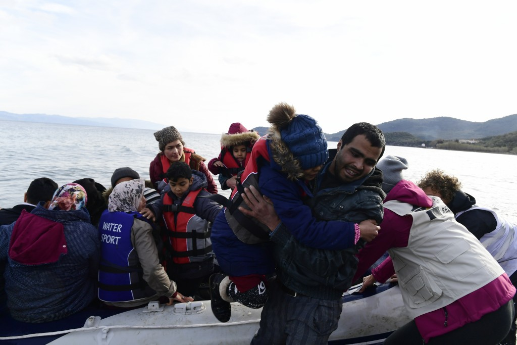 Refugees and migrants arrive with a dinghy at the village of Skala Sikaminias, on the Greek island of Lesbos, after crossing the Aegean sea from Turke...