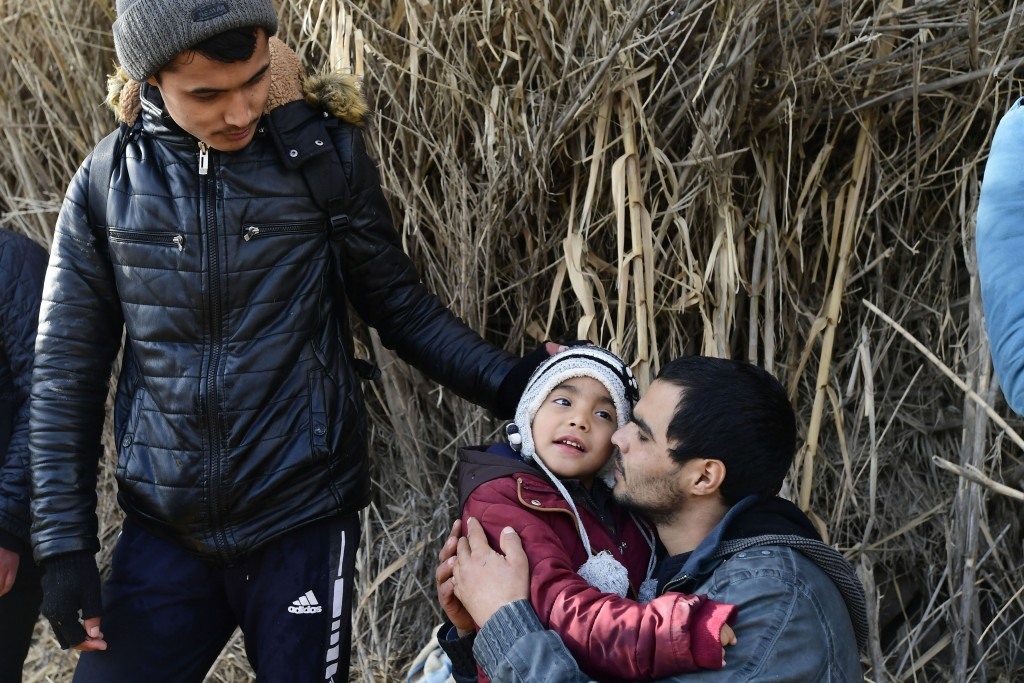 A man hugs a child upon their arrival at the village of Skala Sikaminias, on the Greek island of Lesbos, after crossing the Aegean sea from Turkey wit...