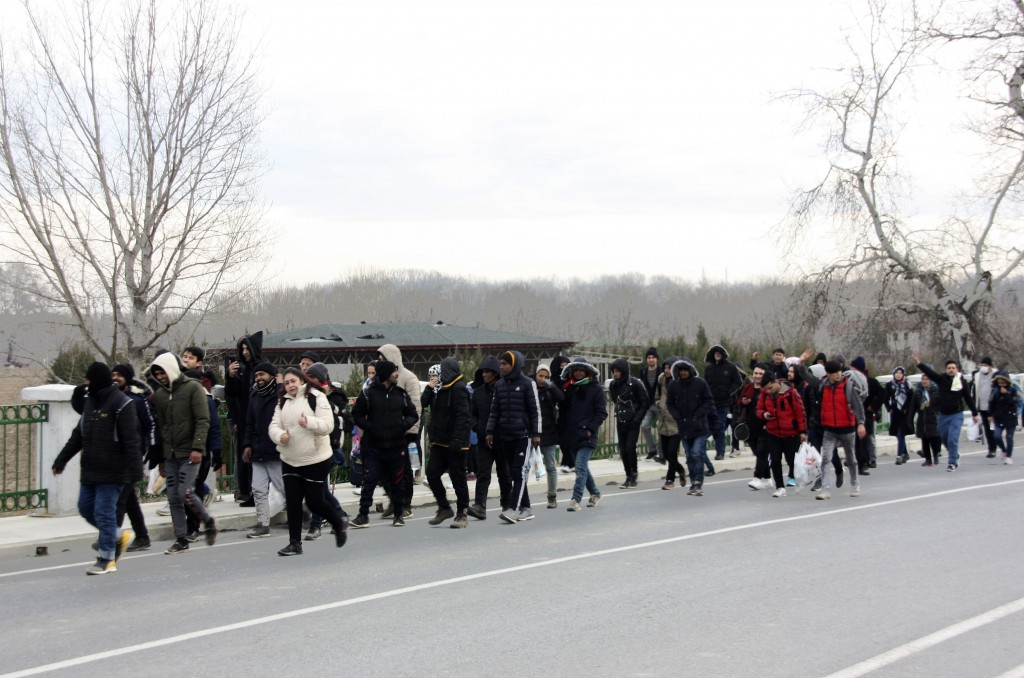 Migrants walk to the border gate of Pazarkule in Edirne, near Turkey-Greece border, early Friday, Feb. 28, 2020. An air strike by Syrian government fo...