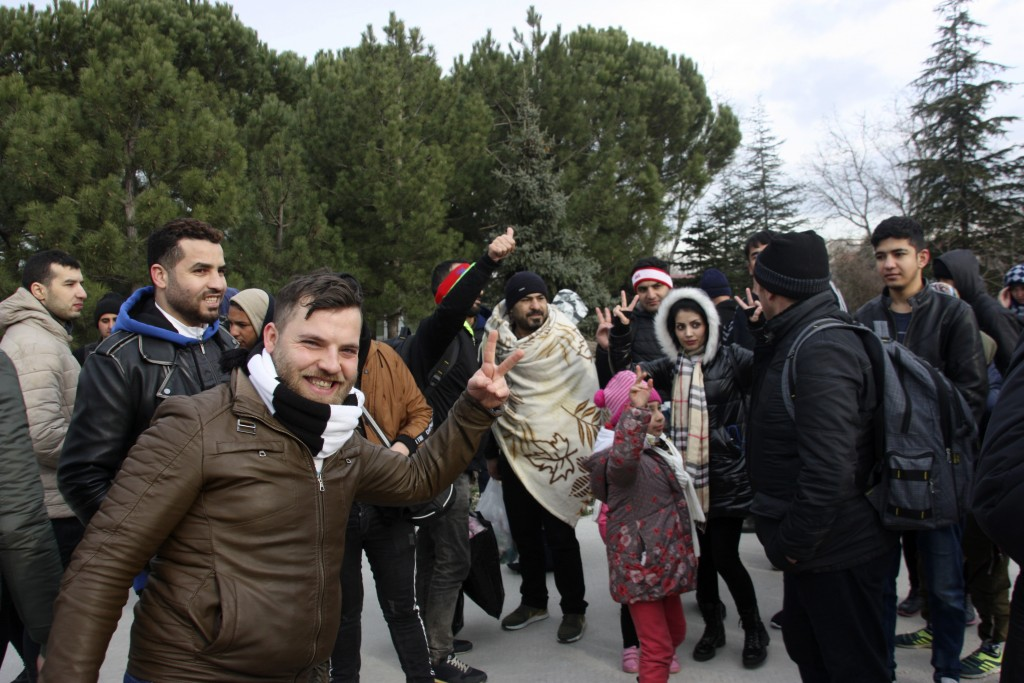 Migrants react as they walk to the border gate of Pazarkule in Edirne, near Turkey-Greece border, early Friday, Feb. 28, 2020. An air strike by Syrian...