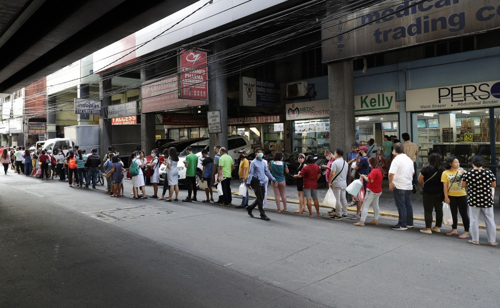 FILE - In this Jan. 30, 2020, file photo, people wait along a road to buy protective face masks at a store in Manila, Philippines. Fear of the spreadi...