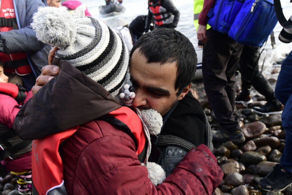 A man hugs a child upon their arrival at the village of Skala Sikaminias, on the Greek island of Lesbos, after crossing the Aegean sea from Turkey, on...