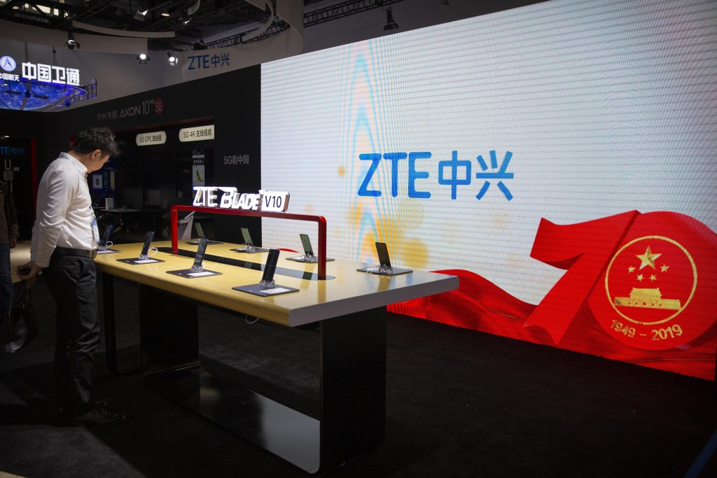 FILE - In this Thursday, Oct. 31, 2019, file photo, a man looks at products from Chinese technology firm ZTE near a screen showing a display commemora...