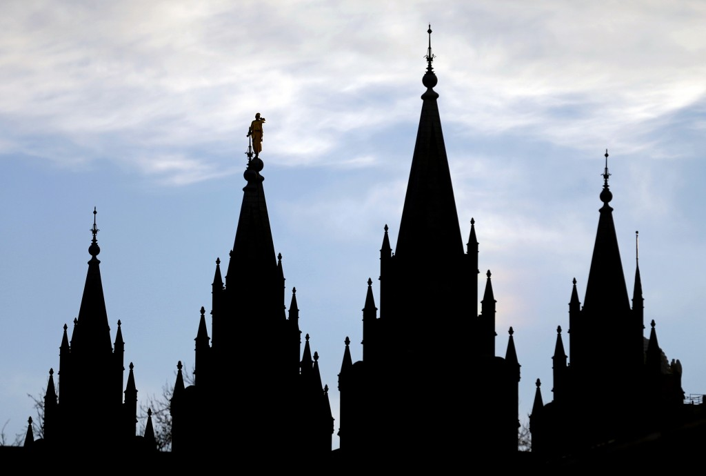 FILE- In this Jan. 3, 2018, file photo, the angel Moroni statue, silhouetted against the sky, sits atop the Salt Lake Temple of The Church of Jesus Ch...