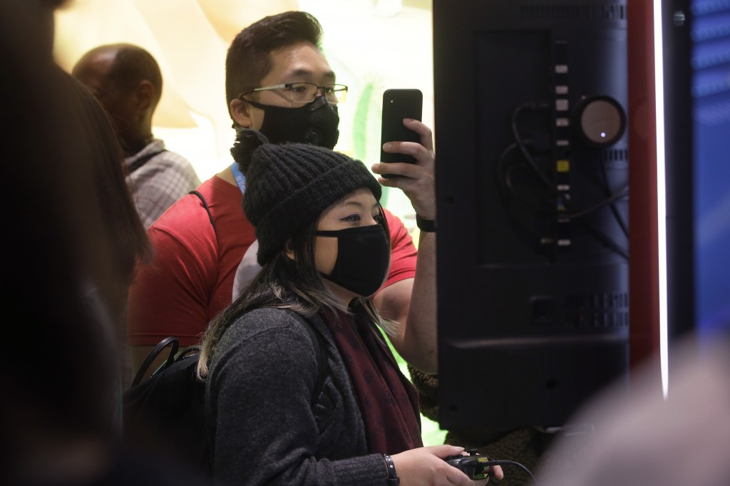 Sonya Tran, of Randolph, Mass., front, and Bobby Ratanasim, of Providence, R.I., behind center, wear protective masks while playing a Nintendo game, T...