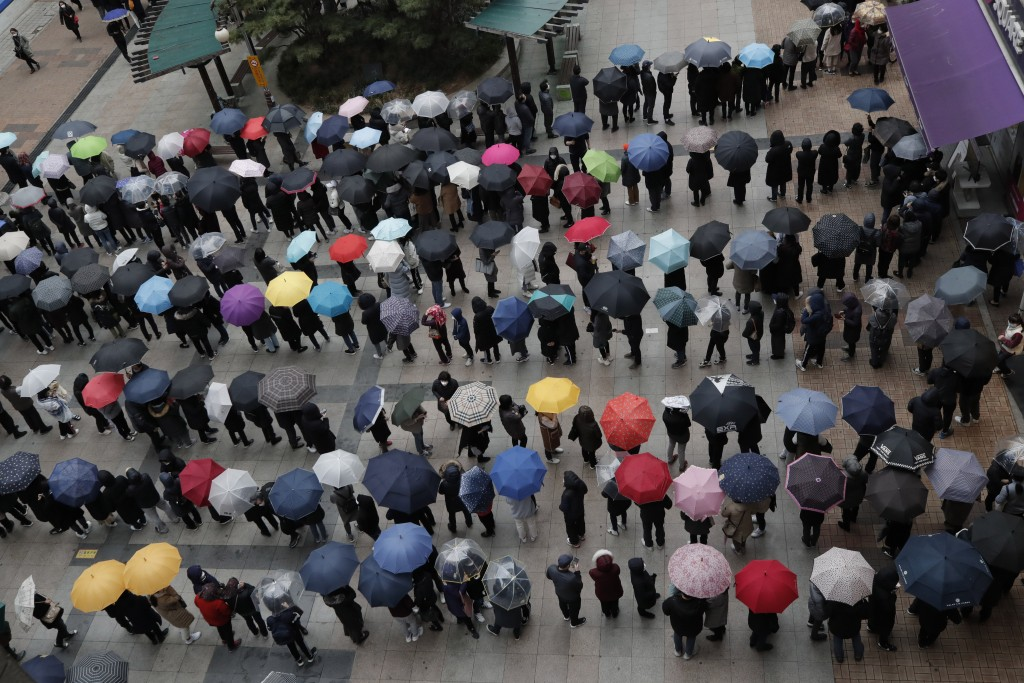 People wearing masks line up to buy face masks to protect themselves from the coronavirus outside a department store in Seoul, South Korea, Friday, Fe...
