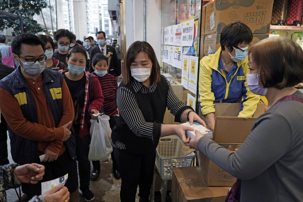 FILE - In this Feb. 7, 2020, file photo, people queue up to buy face masks in Hong Kong. Fear of the spreading coronavirus has led to a global run on ...