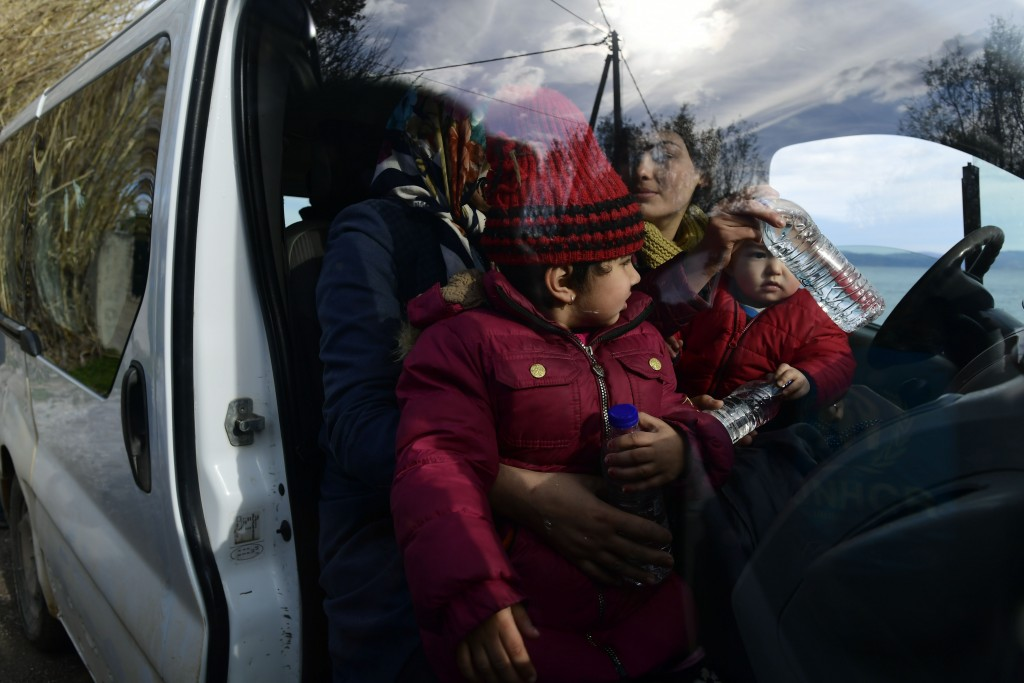 Migrants sit inside a vehicle upon their arrival at the village of Skala Sikaminias, on the Greek island of Lesbos, after crossing the Aegean sea from...
