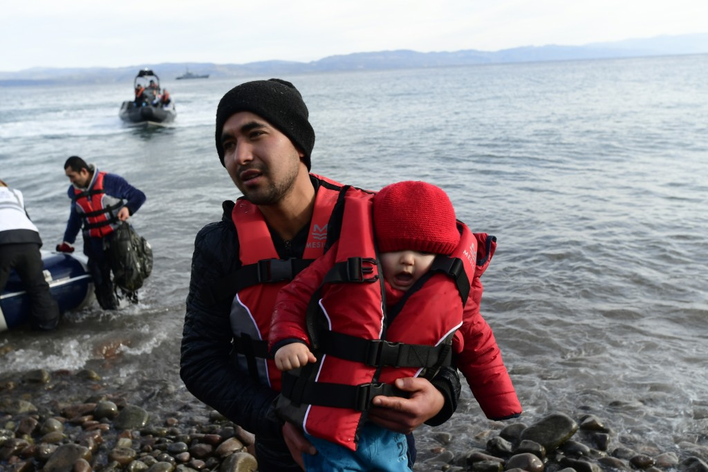 A migrant holds a baby as they arrive at the village of Skala Sikaminias, on the Greek island of Lesbos, after crossing the Aegean sea from Turkey, on...