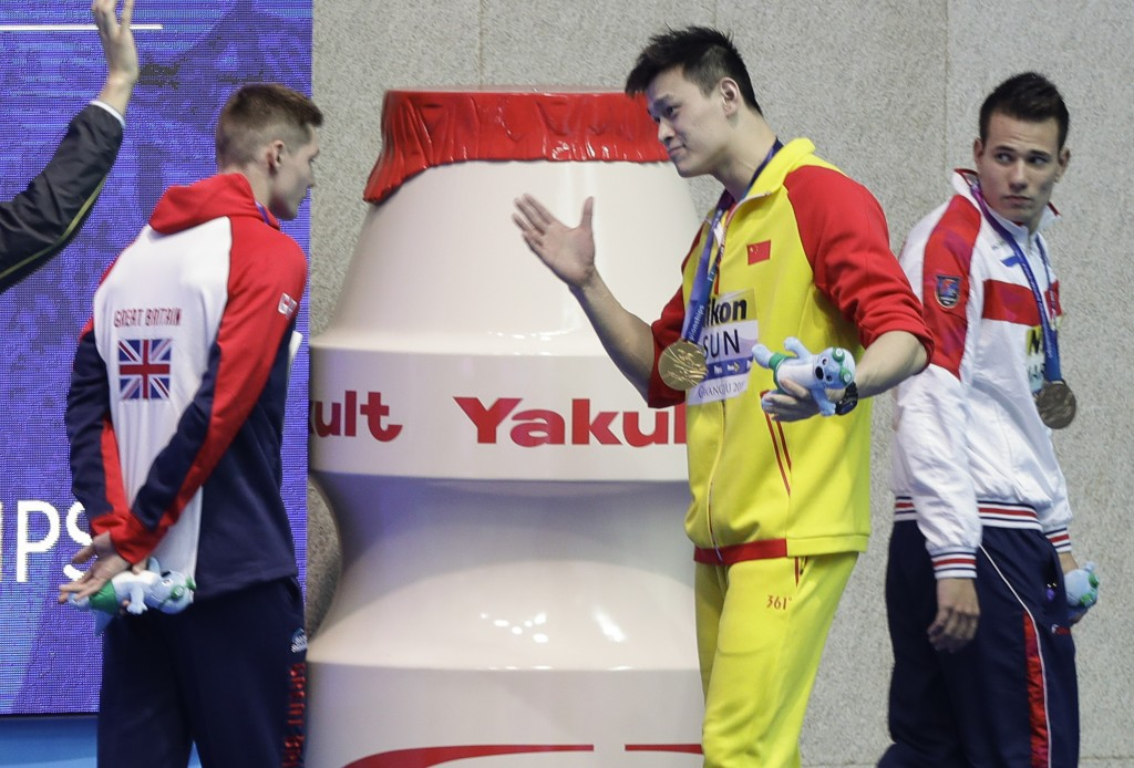 FILE - In this Tuesday, July 23, 2019 file photo, gold medalist China's Sun Yang, centre, gestures to Britain's bronze medalists Duncan Scott, left, f...