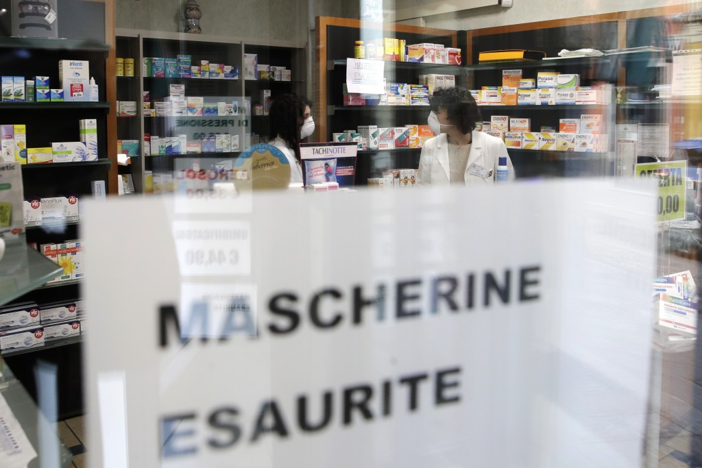 """FILE - In this Feb. 22, 2020, file photo, a note reading in Italian """"Masks sold out"""" hangs on the window of a pharmacy in Codogno, near Lodi, Northern..."""