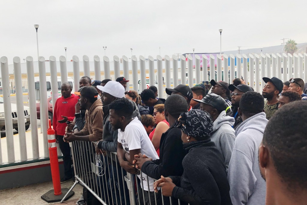 FILE - In this Sunday, July 28, 2019, file photo, migrants in Tijuana, many from Cameroon, listen to names being called for those who can claim asylum...