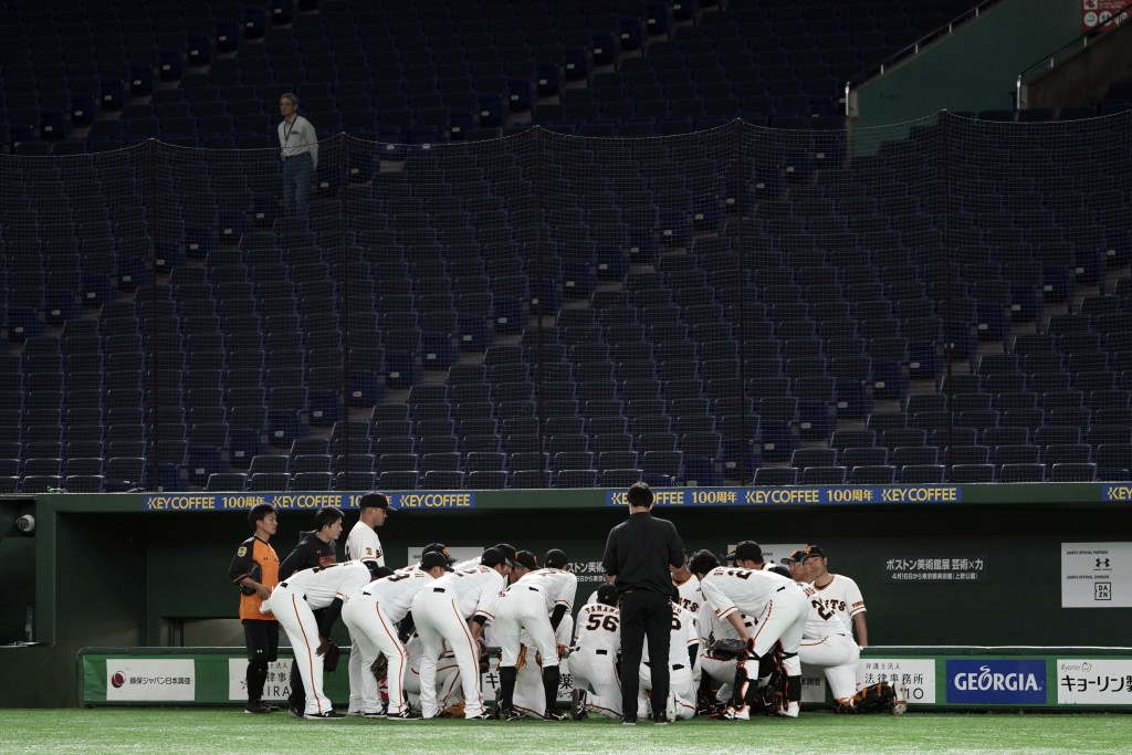 Spectators' stands are empty during a warm up session in a preseason baseball game between the Yomiuri Giants and the Yakult Swallows at Tokyo Dome in...