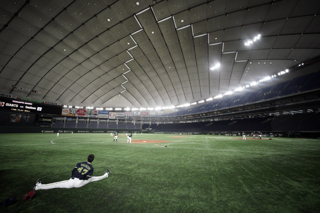 A player stretches where spectators' stands are empty prior to a preseason baseball game between the Yomiuri Giants and the Yakult Swallows at Tokyo D...