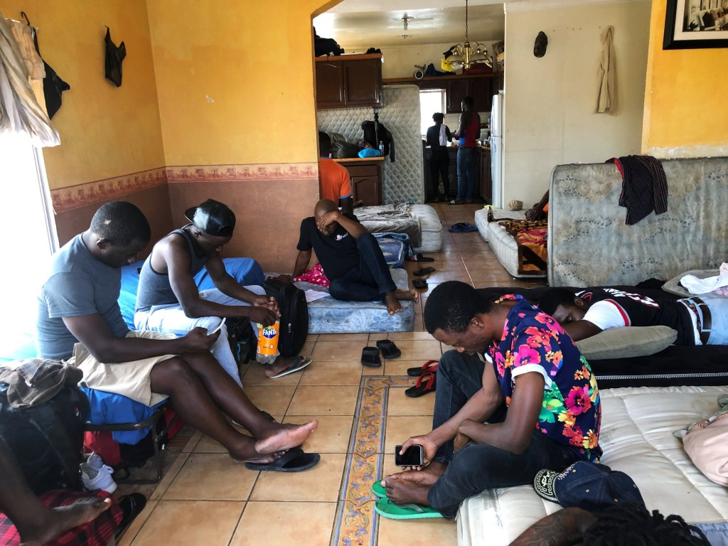 FILE - In this July 28, 2019, file photo, Cameroonians wait in a rented apartment in Tijuana, Mexico, until their names are called to claim asylum in ...