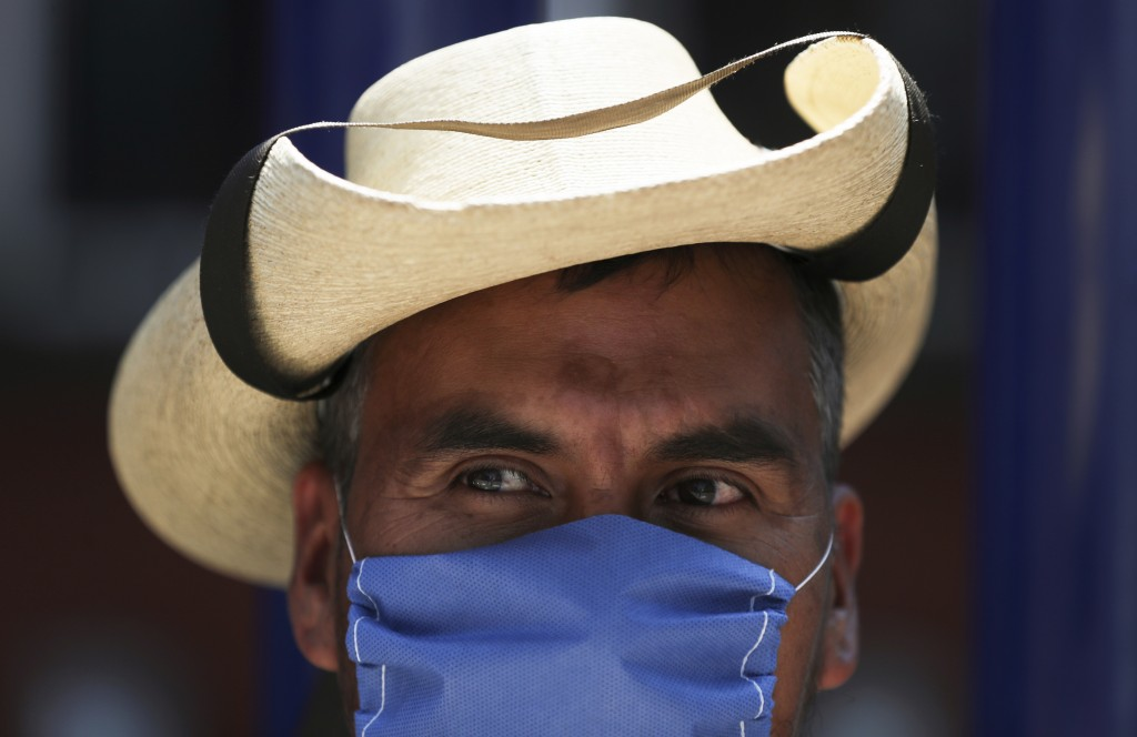 A street vendor wears a mask over his mouth as a precaution against the spread of the new coronavirus in Mexico City, Friday, Feb. 28, 2020. Mexico's ...
