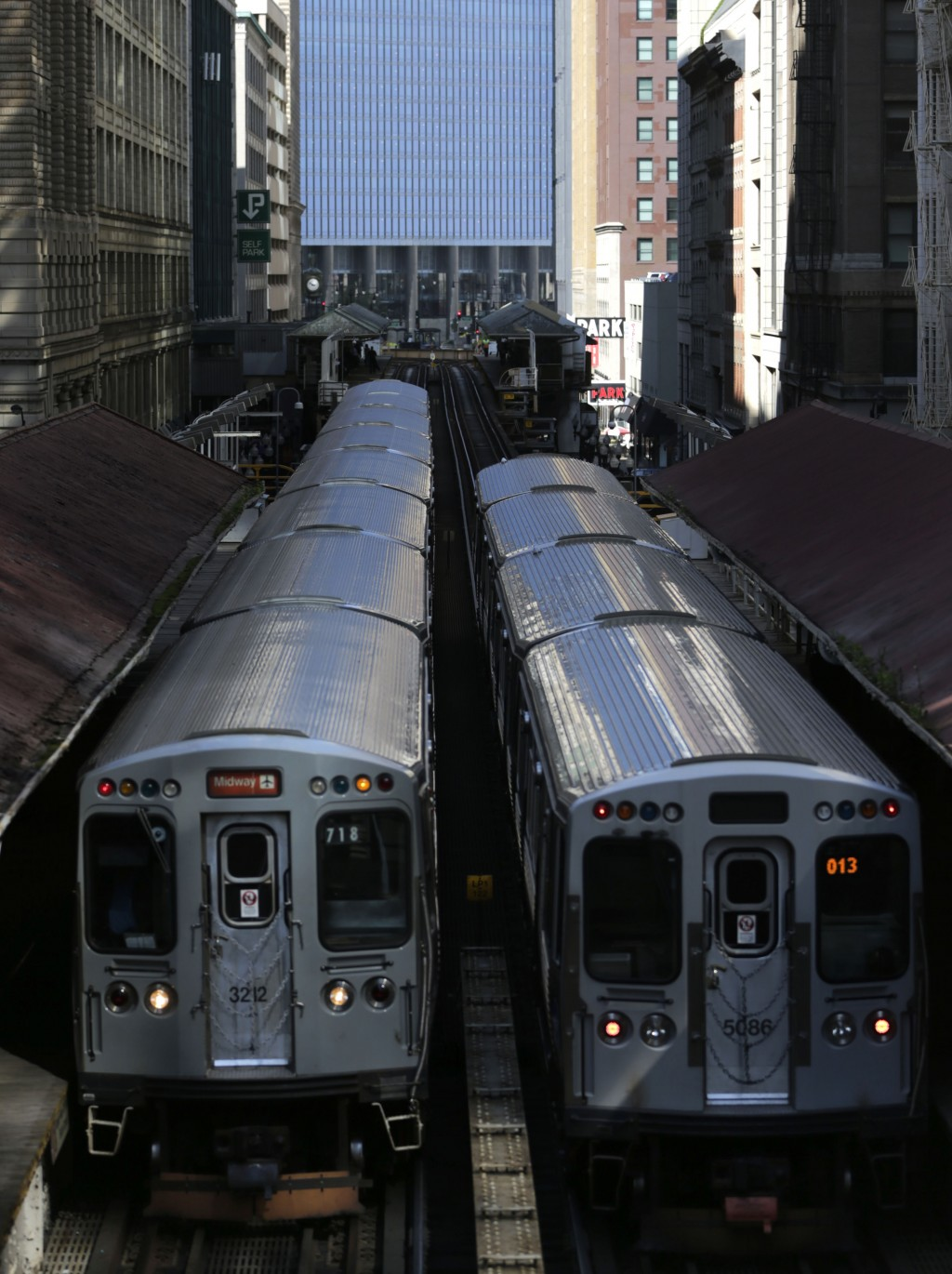 FILE - In this Sept. 17, 2014 file photo, two Chicago Transit Authority elevated trains can be seen above Wabash Avenue in Chicago's famed Loop. A spi...