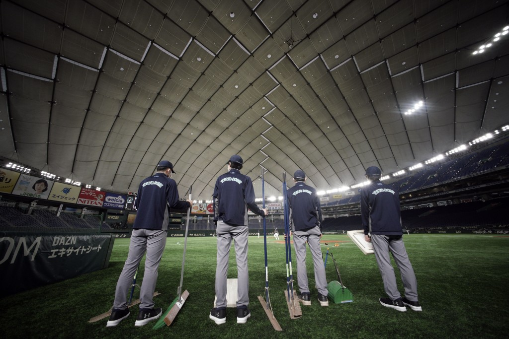 Staffs stand where spectators' stands are empty prior to a preseason baseball game between the Yomiuri Giants and the Yakult Swallows at Tokyo Dome in...