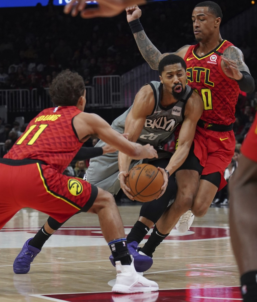 Brooklyn Nets Spencer Dinwiddie (26) tries to drive past Atlanta Hawks Trae Young (11) John Collins in the first half of an NBA basketball game Friday...