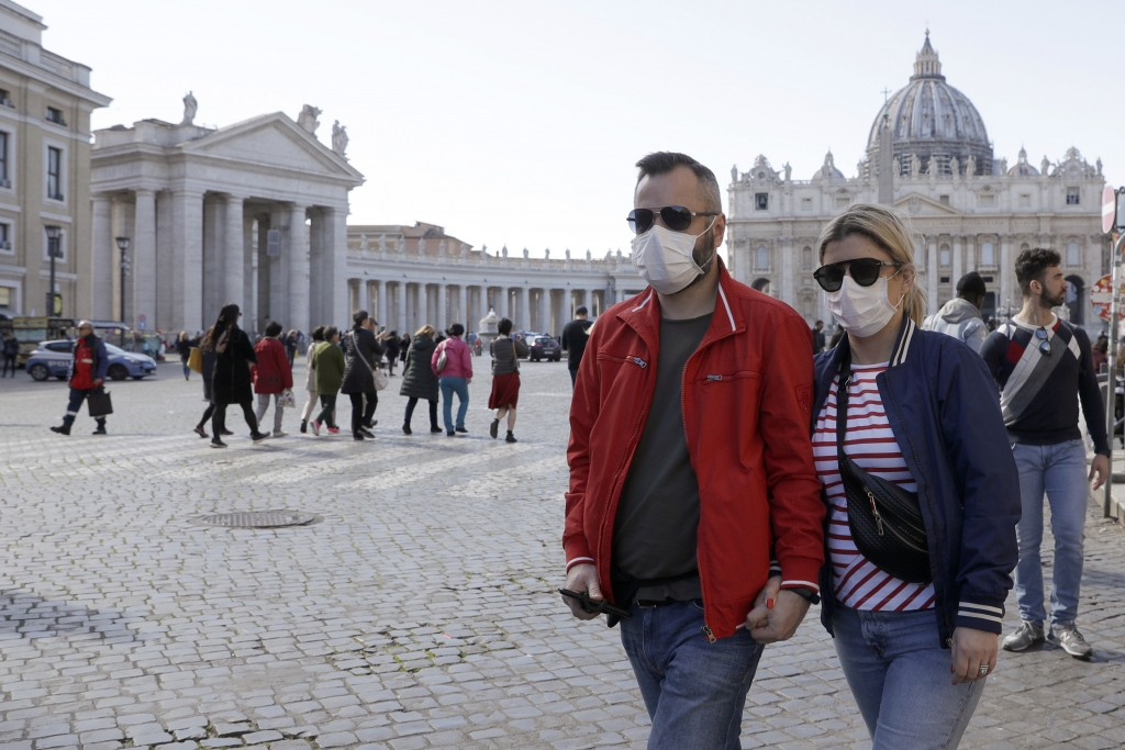 FILE - In this Thursday, Feb. 27, 2020 file photo, a couple wearing face masks stroll outside St. Peter's Square, at the Vatican. A U.S. government ad...