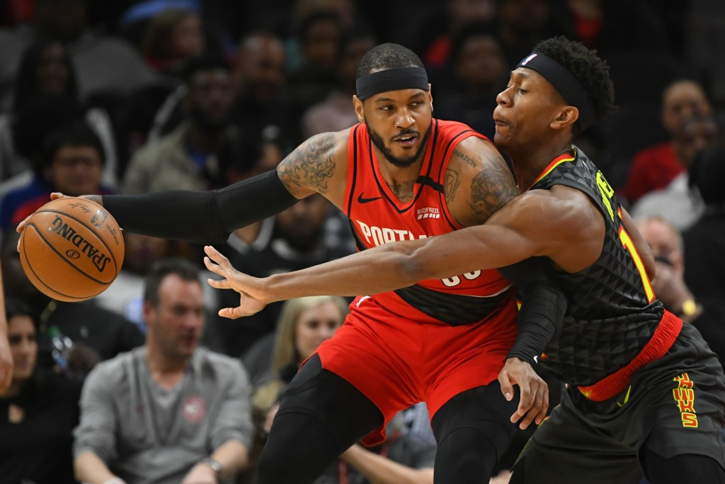 Portland Trail Blazers forward Carmelo Anthony, left, tries to keep the ball from Atlanta Hawks forward De'Andre Hunter during the first half of an NB...
