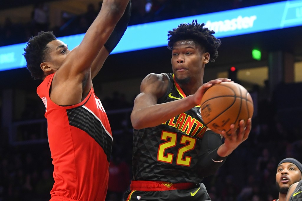Atlanta Hawks guard Cam Reddish (22) goes high under the basket as Portland Trail Blazers center Hassan Whiteside defends during the first half of an ...
