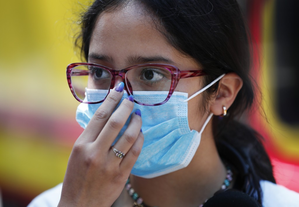 A teen wears a medical mask as a precaution against the spread of the new coronavirus, during an outing in Mexico City, Saturday, Feb. 29, 2020. Mexic...
