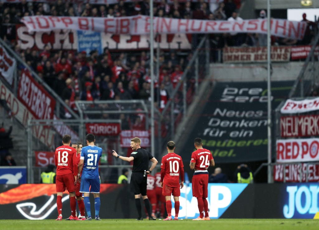 "Referee Christian Dingert, center, talks to Hoffenheim and Munich players while Munich fans on the tribune display a banner reading ""Hopp stays a son ..."