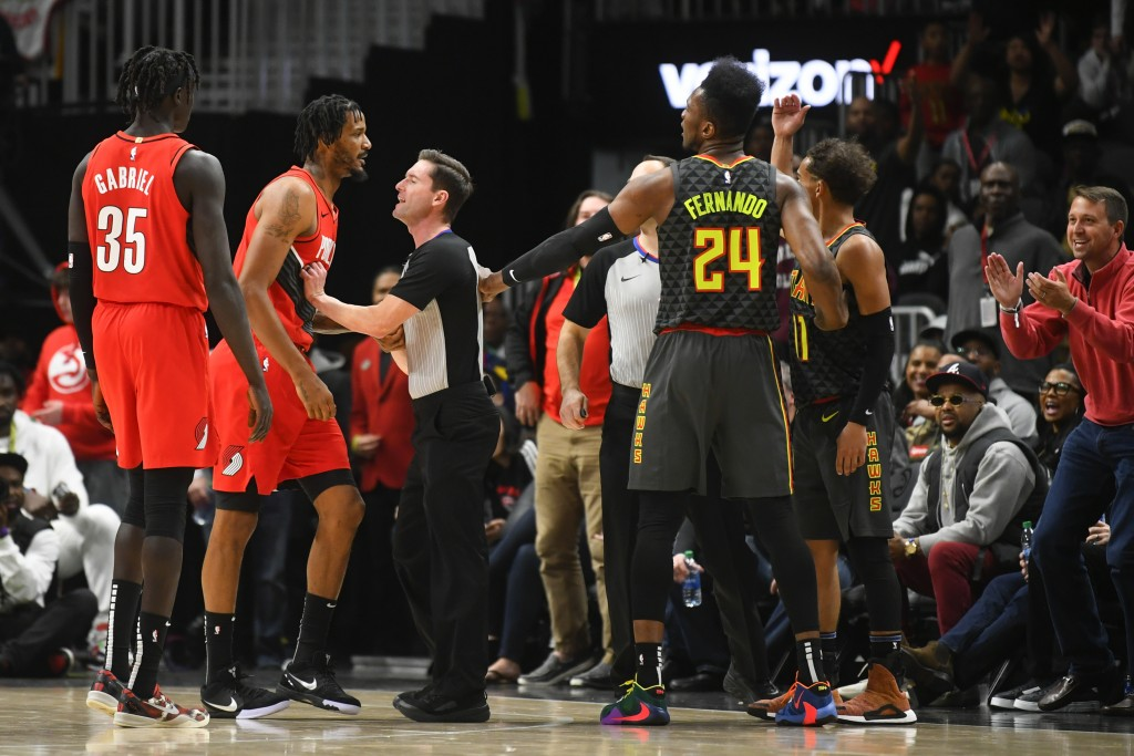 A referee, third from left, keeps Portland Trail Blazers forward Trevor Ariza, second from left, and Atlanta Hawks guard Trae Young (11) separated dur...