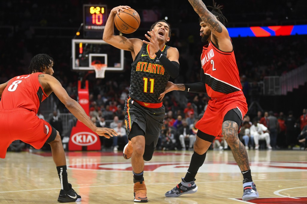 Atlanta Hawks guard Trae Young (11) tries to penetrate the defense of Portland Trail Blazers forward Trevor Ariza (8) and guard Gary Trent Jr. (2) dur...