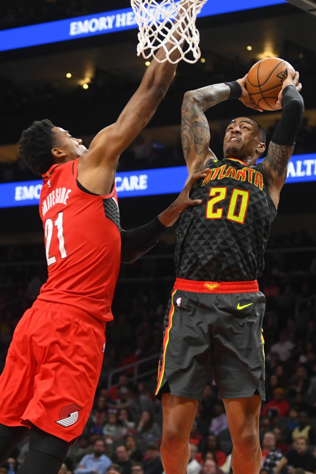 Atlanta Hawks forward John Collins (20) shoots as Portland Trail Blazers center Hassan Whiteside defends during the first half of an NBA basketball ga...
