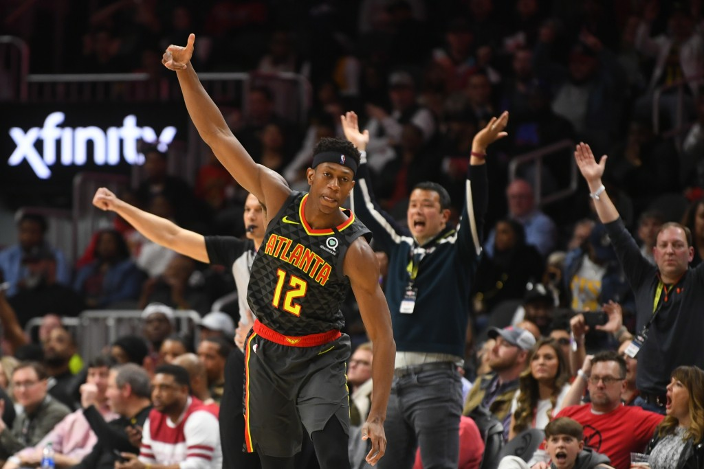 Atlanta Hawks forward De'Andre Hunter (12) reacts after scoring against the Portland Trail Blazers during the second half of an NBA basketball game Sa...