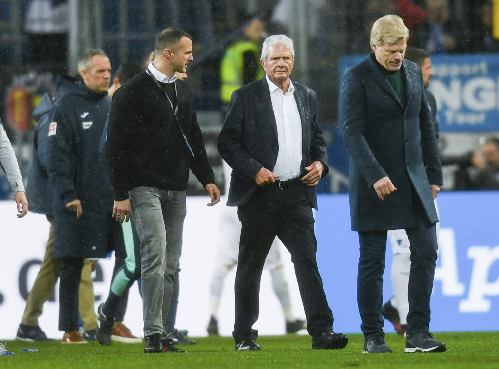 Dietmar Hopp, center, patron of TSG 1899 Hoffenheim, and former soccer player and board member of FC Bayern Munich, Oliver Kahn, leave the field after...