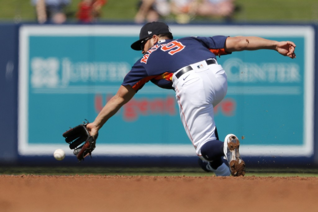 Houston Astros shortstop Jack Mayfield dives for a ground ball single by New York Mets' Michael Conforto during the third inning of a spring training ...