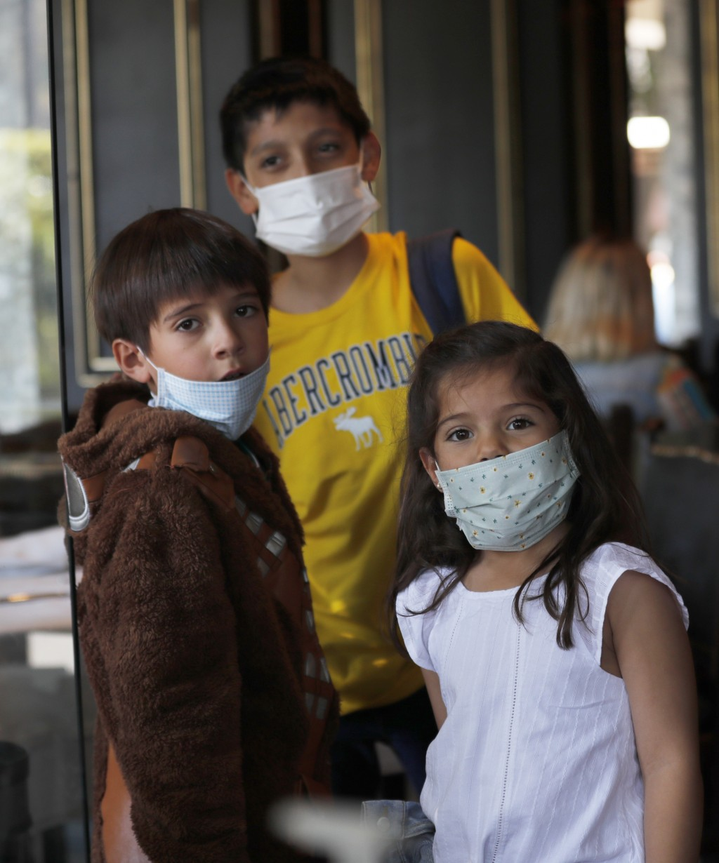 A trio of cousins wear medical masks as a precaution against the spread of the new coronavirus, during an outing to a restaurant in Mexico City, Satur...
