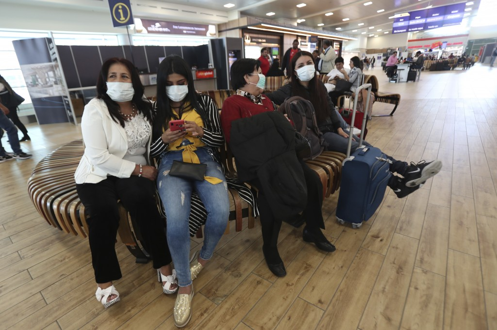 People wearing face masks wearing masks wait for the arrival of their relatives at the Mariscal Sucre International Airport, in Quito, Ecuador, Saturd...