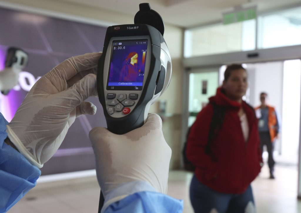 A Health Ministry staffer monitors the body temperature of travelers deplaning from international flights at the Mariscal Sucre Airport, in Quito, Ecu...