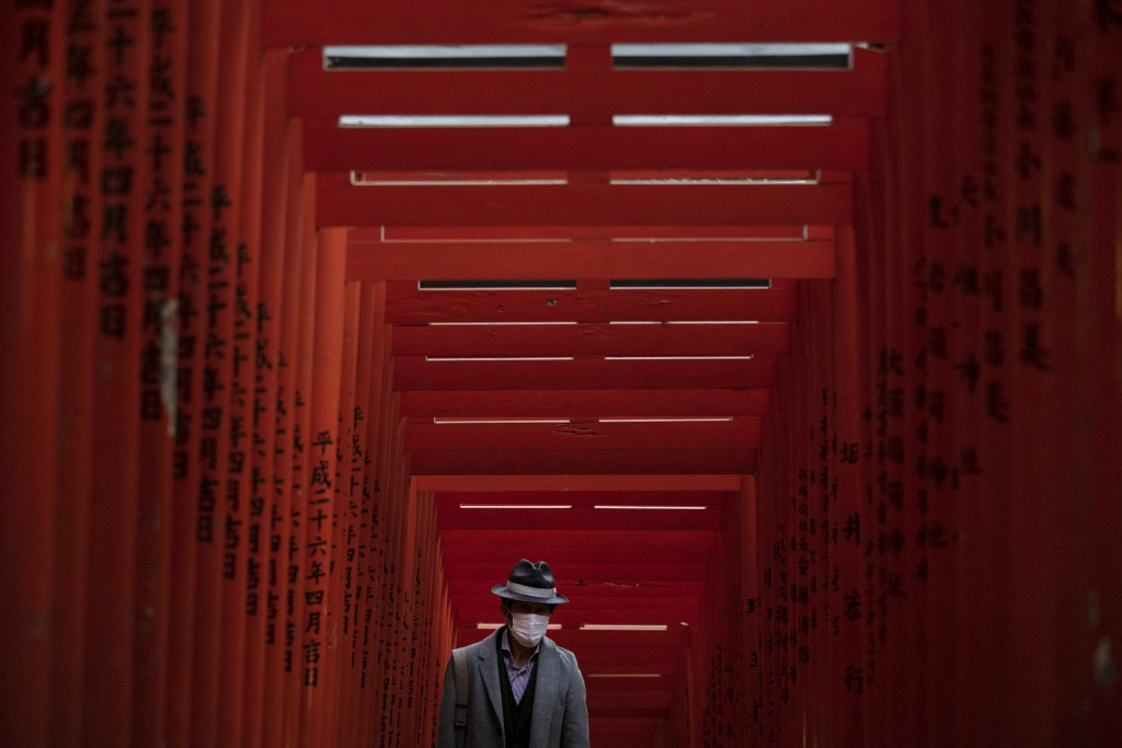 A man with a mask walk through torii gates at the Hie Shrine In Tokyo, Sunday, March 1, 2020. The coronavirus has claimed its first victim in the Unit...