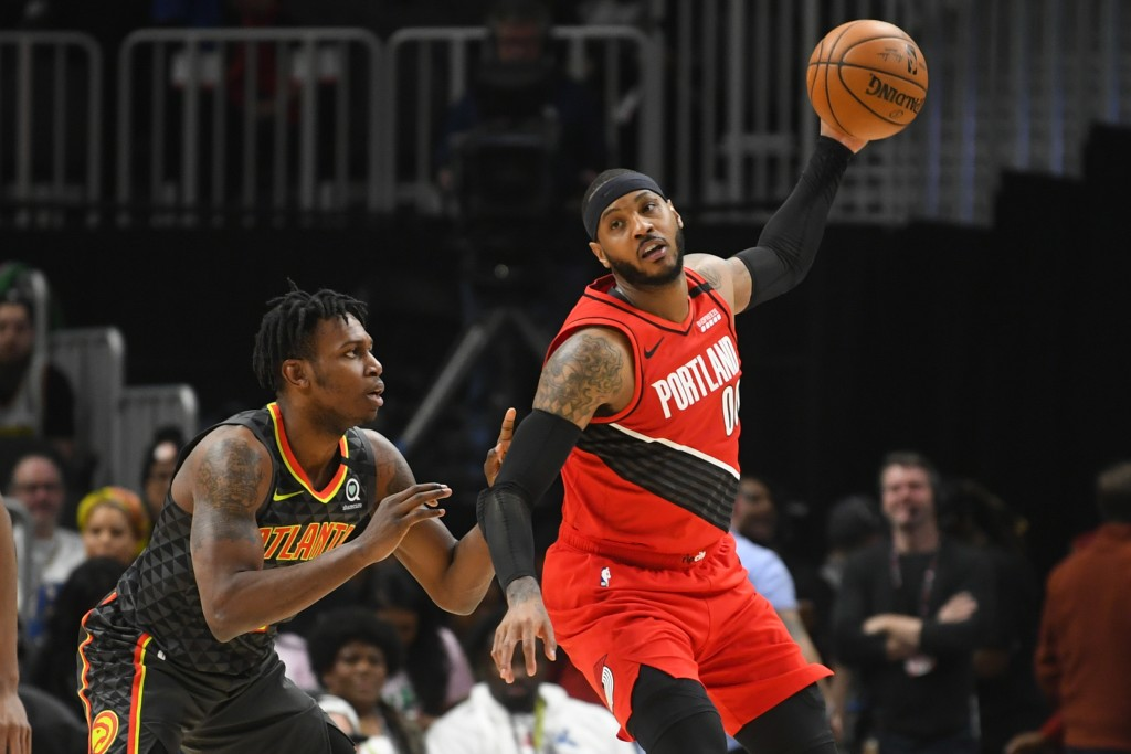 Portland Trail Blazers forward Carmelo Anthony, right, keeps the ball high away from Atlanta Hawks guard Treveon Graham, left, during the first half o...