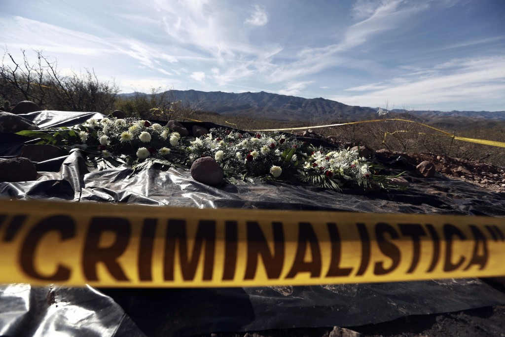 FILE - This Jan. 12, 2020 file photo shows flowers placed by relatives on the remains where one of the cars belonging to the extended LeBaron family w...