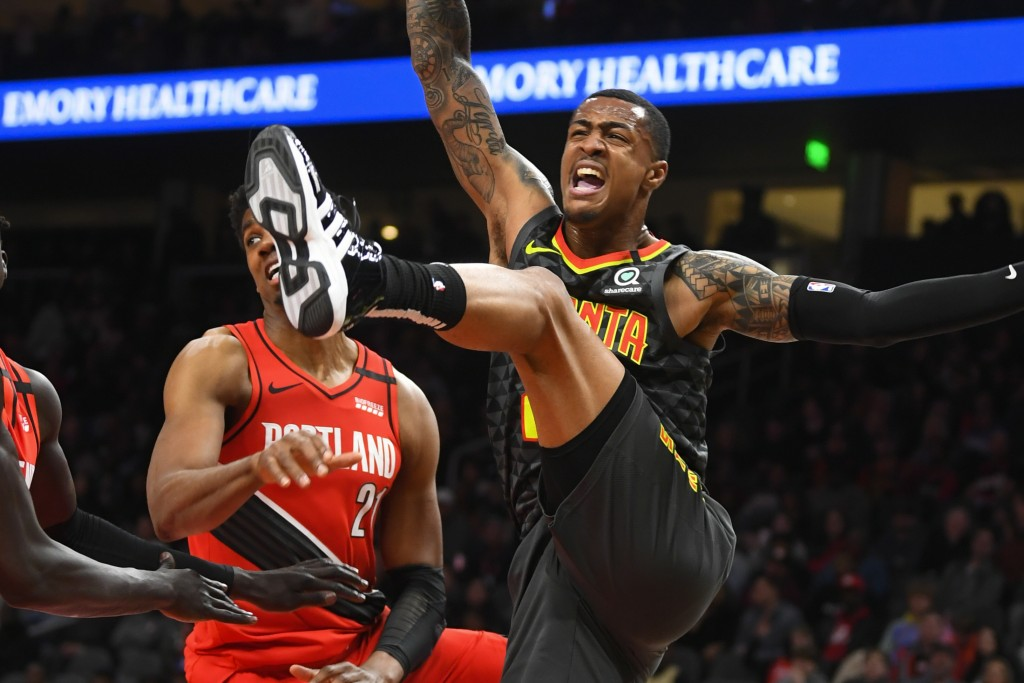 Atlanta Hawks forward John Collins, right, comes down from being fouled while shooting by Portland Trail Blazers center Hassan Whiteside during the fi...