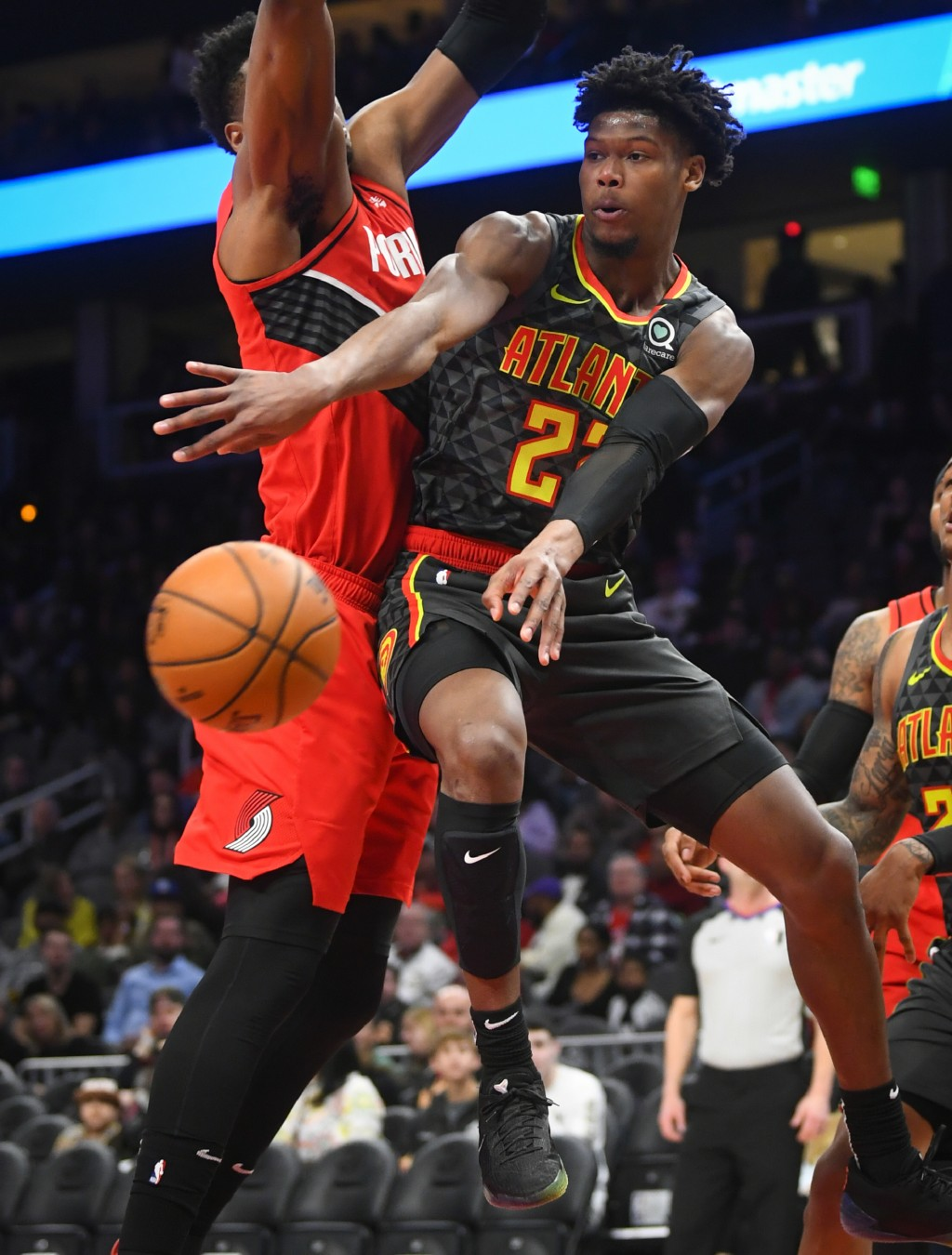 Atlanta Hawks guard Cam Reddish, right, dishes off while guarded by Portland Trail Blazers center Hassan Whiteside, left, during the first half of an ...