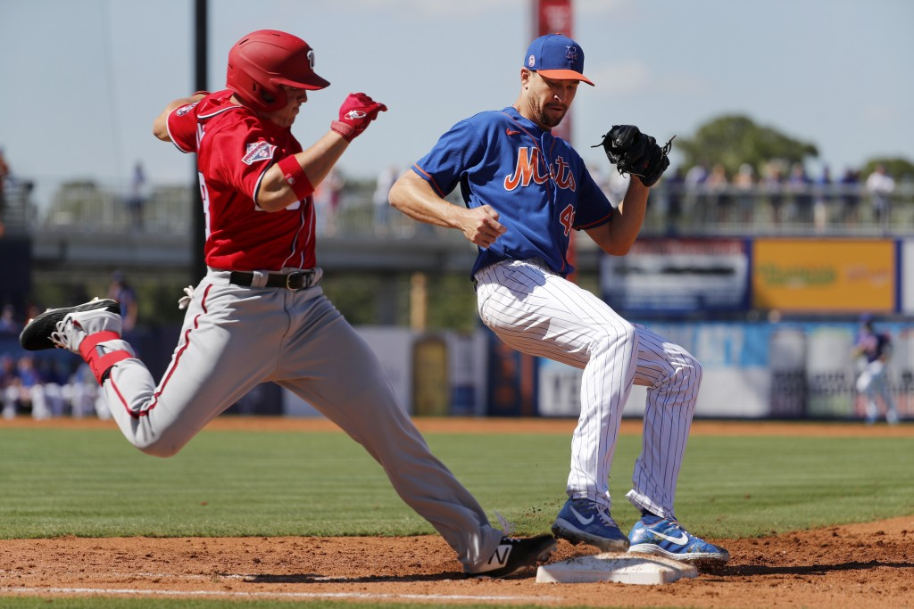 New York Mets pitcher Jacob deGrom, right, forces Washington Nationals' JB Shuck out at first base to end the top of the third inning of a spring trai...